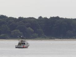 A police boat is stationed near the opening to the Long Island Sound in Lloyd Harbor, N.Y., on Thursday.