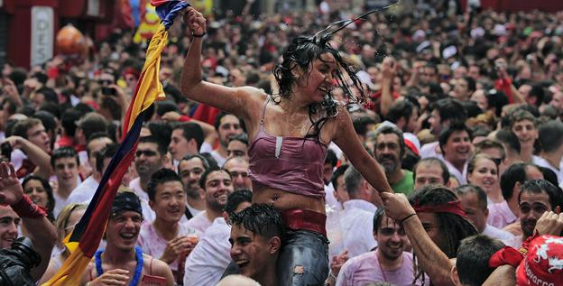 A reveler carries a young woman on his shoulders in Ayuntamiento square, in Pamplona, northern Spain, on Friday during celebrations at the start of Spain's most famous bull-running festival.