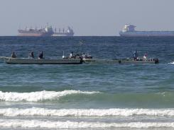 Fishing boats are seen in front of oil tankers on the Persian Gulf waters, south of the Strait of Hormuz on Jan. 19.
