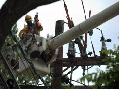 A Pepco employee works July 1 to stabilize power lines damaged in a massive storm that swept through the region in Bethesda, Md.