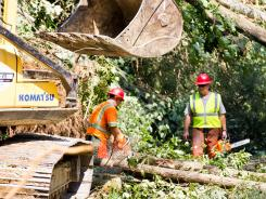 Workers clear storm damage from Great Smoky Mountains National Park on Saturday near Townsend, Tenn.
