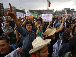 Demonstrators shout slogans as they gather at the Zocalo Plaza in Mexico City on Saturday.