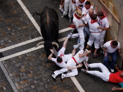 A Miura fighting bull collides with a runner along the Estafeta Street in Pamplona, Spain.