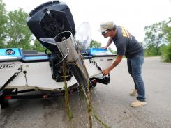 An invasive plant species hangs from the propeller of Brian Griffin's boat as he takes it out of Loon Lake in Antioch, Ill.