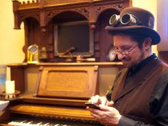 Michael Dashow of Oakland checks his smartphone in front of a steampunk invention that is part piano, part computer screen at the Clockwork Alchemy convention.
