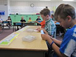 Dillon Elledge, 8, right, and Brody Kemble, 7, work with flash cards in their all-boys classroom at Middleton Heights Elementary in Middleton, Idaho.