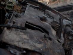 A destroyed Syrian army tank is abandoned Wednesday on the side of a highway between Aleppo and Damascus.