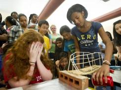 Math scholars: At a June institute in Memphis, Claire Gerling, 12, covers her eyes as her partner, Amara Bryson, 12, adds sand to a bucket suspended below a wooden bridge .