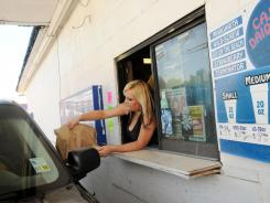 Nicole Brettillo serves frozen daiquiris to customers through the drive-through window at Cajun Liquor in Shreveport, La.