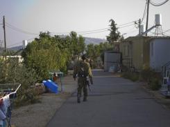 An Israeli soldier walks in the unauthorized West Bank Jewish outpost of Nofei Nehemya on Monday.