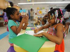 "Alicia Green, 6, left, reads while Kristina Smith, 6, records the books she has read in the ""Camping Out With Books"" room during a summer school program at Langston Hughes Elementary School in Baltimore."
