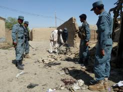 Afghanistan policemen stand at the site of a suicide attack in Kandahar on Monday.