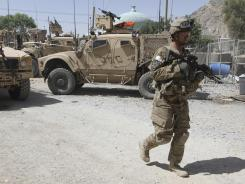A U.S. soldier, part of the NATO forces, patrols a police station after it was attacked by militants in Kandahar, Afghanistan, on June 19.