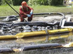 A worker checks water in Talmadge Creek on July 29, 2010, in Marshall Township, Mich. Oil had spilled from a ruptured pipeline.