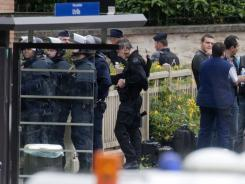 Police officers surround a school complex where an armed man took hostages Tuesday in Vitry sur Seine, south of Paris.