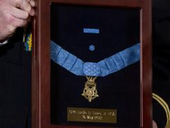 A military aid holds the Medal of Honor during a ceremony at the White House.