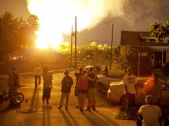 People watch flames shoot up from a freight train that derailed early Wednesday in Columbus, Ohio.