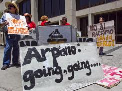 Protesters carry signs outside the offices of Sheriff Joe Arpaio on June 25, several hours after the U.S. Supreme Court upheld one provision of Arizona's immigration law and struck down the other three as unconstitutional.