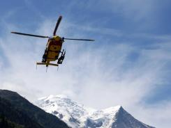 A rescue helicopter lands in Chamonix, French Alps, after returning from an avalanche site Thursday.