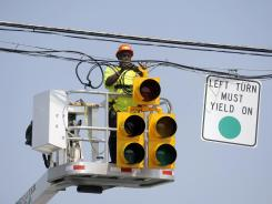 After the storm: A worker ties power lines above a traffic signal on July 1 in Lynchburg, Va. A storm with 80-mph winds hit June 29 and left millions without power in the Midwest and the East Coast.