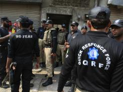 Pakistan's police commandos stand outside a Lahore house attacked by gunmen on Thursday.