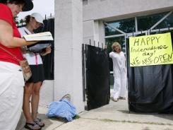 While abortion opponents pray, left, Jackson Women's Health Organization owner Diane Derzis poses at the gate of Mississippi's only abortion clinic in Jackson, Miss., July 2.