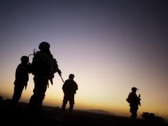 U.S. soldiers patrol the outskirts of Spin Boldak, Afghanistan. A panel recommended Friday that soldiers returning from Iraq and Afghanistan be screened for post-traumatic stress disorder at least once a year.