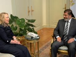 Egyptian President Mohamed Morsi and Hillary Clinton talk at the presidential palace in Cairo on Saturday.
