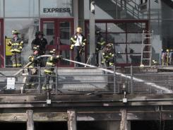 Firefighters work to extinguish a fire Saturday at Pier 17 in New York.