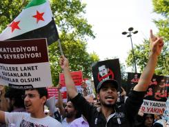 Demonstrators protest against the killing of more than 100 people in Syria.