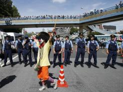 An anti-nuclear protester dressed as a clown is watched by police officers during a rally in downtown Tokyo Monday.