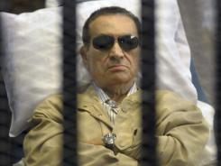 Egypt's ex-president Hosni Mubarak lies on a gurney inside a barred cage in the police academy courthouse in Cairo on June 2.