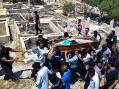 Syrian mourners carry the coffin of Ali Otri Salim during his funeral in Al-Tal in the outskirts of Damascus, Syria, July 7.