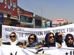 "Afghan women hold a banner reading, ""Where is the protection and justice for Afghan women?"" during a protest in Kabul over the execution of a woman by insurgents."