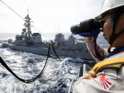 A crewmember aboard Japanese Maritime Self-Defense Force supply ship AOE-423 Tokiwa patrols the surrounding waters in this June 2009 file photo.