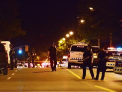 Police stand guard early Tuesday near the scene of a deadly shooting in Toronto.