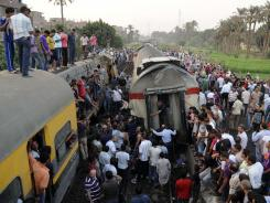 Bystanders gather around a derailed train in Badrashin in Giza, Egypt, on Tuesday.