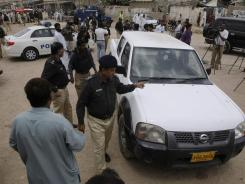 Pakistani police officers gather by a vehicle that was attacked Tuesday in Karachi. A doctor working on a polio immunization program was wounded.