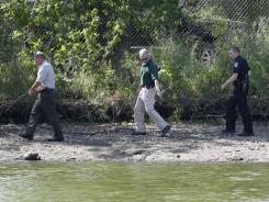 Law enforcement authorities collect possible evidence Tuesday near Iowa's Meyers Lake, where Lyric Cook-Morrissey and Elizabeth Collins disappeared.