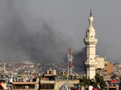 Smoke billows over Damascus, Syria, on Wednesday after a bomb ripped through a high-level security meeting.