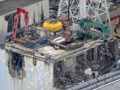 Aerial view shows the damaged No. 4 reactor building at Tokyo Electric Power Co.'s Fukushima Dai-ichi nuclear power plant, where a crane removed two rods packed with nuclear fuel from the reactor building.