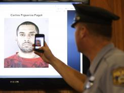 A police officer snaps an image with his phone of a booking photo of Carlos Figueroa-Fagot before a news conference Thursday in Philadelphia.