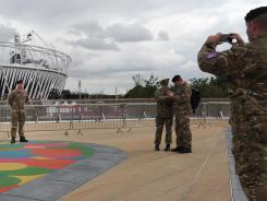 A soldier has his photo taken Thursday in front of the Olympic Stadium in east London.