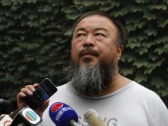Dissident artist Ai Weiwei listens as his lawyer announces over speakerphone the verdict of Ai's lawsuit against the Beijing tax authorities in Beijing on Friday.