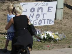 "A woman and a child stand near a sign that reads ""7/20 Gone Not Forgotten,"" near the Colorado movie theater where a gunman killed 12 people and wounded dozens of others in one of the deadliest mass shootings in recent U.S. history."