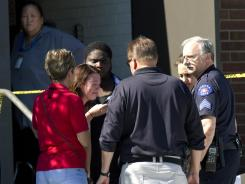 A woman overcome with emotion is surrounded by counselors, police and clergy outside Gateway High School where witnesses are being interviewed by authorities.