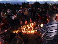 People attend a candlelight prayer gathering on Friday in Aurora, Colo.
