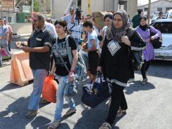 Syrians carry their belongings as they cross into Lebanon at the border crossing point in Masnaa, eastern Lebanon.