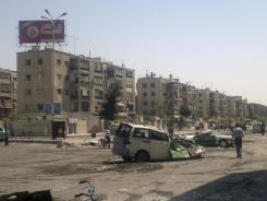 Syrians walk past destroyed vehicles after fighting between rebels and troops in south Damascus.