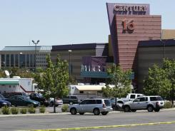 Police and other vehicles remain in front of the Century 16 movie theater Saturday, in Aurora, Colo., where 12 people were killed and dozens injured in a shooting attack.